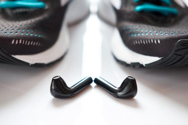 Sneakers nere per corsa con elementi verdi e lacci verdi e cuffie nere si trovano su uno sfondo bianco.