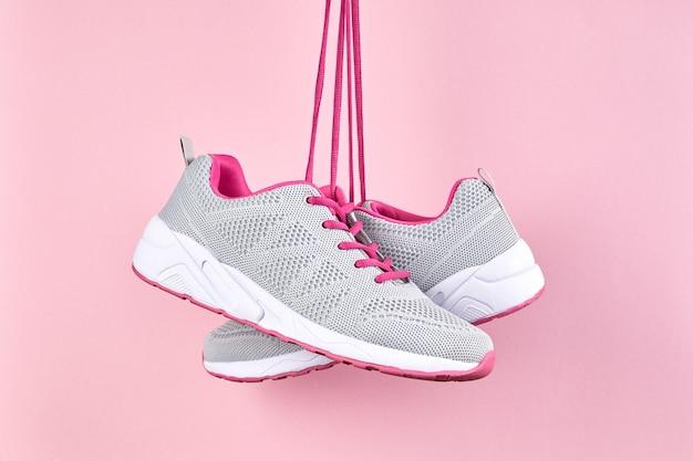 Sneakers sportive femminili per corsa e fitness su sfondo rosa. moda scarpe sportive alla moda, da vicino
