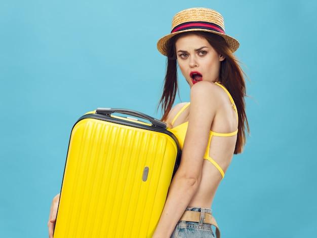 Snella bella donna si sta preparando per le vacanze e raccoglie una valigia, una valigia gialla, un cappello da costume da bagno, un'immagine per le vacanze