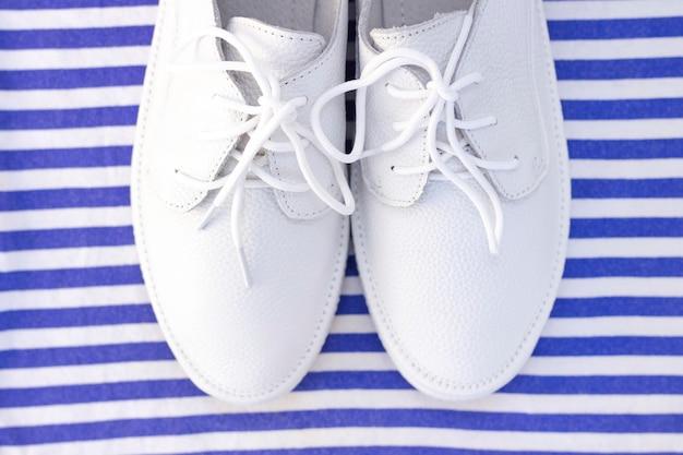 Snickers bianchi su uno sfondo bianco-blu a strisce