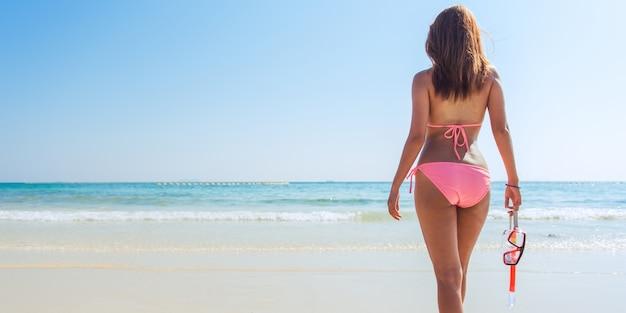 Snorkeling snorkeling vacanza sulla spiaggia con maschera e pinne. donna bikini rilassante sulla fuga tropicale estiva facendo attività snorkeling con snorkeling pipi flippers solare abbronzatura. banner coltura per lo spazio di copia