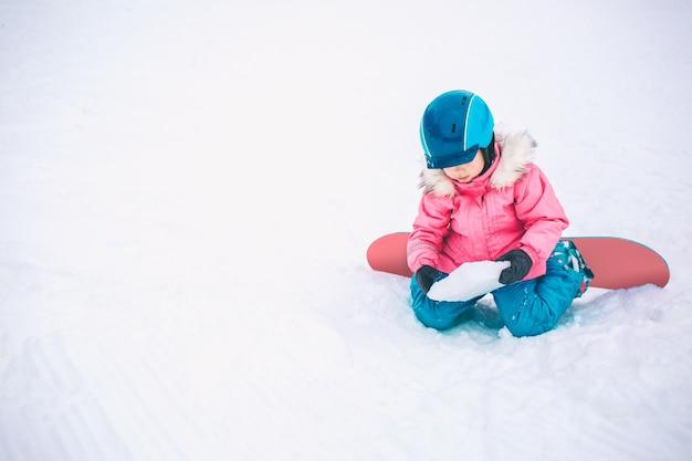 Snowboard sport invernali. ragazza del bambino che gioca con la neve che indossa vestiti caldi di inverno. inverno