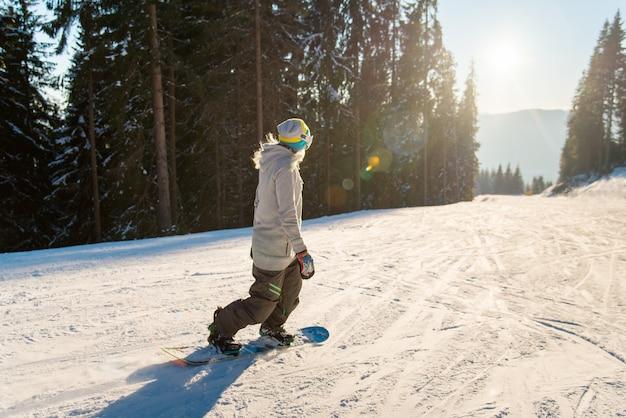 Snowboarder a cavallo in montagna in una giornata invernale di sole