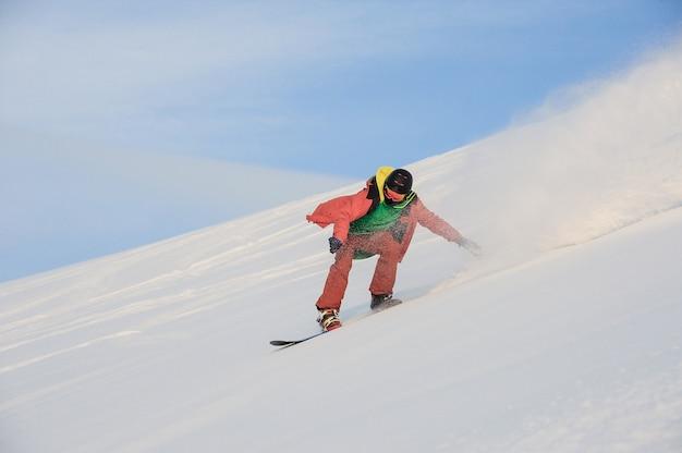Snowboarder attivo che guida sul pendio nevoso