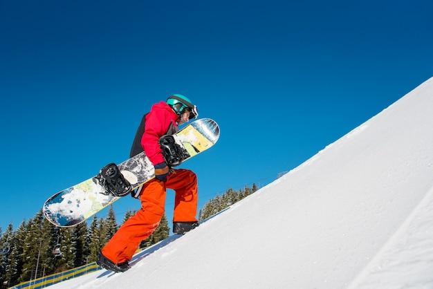 Snowboarder che cammina su per il pendio alla stazione sciistica di inverno