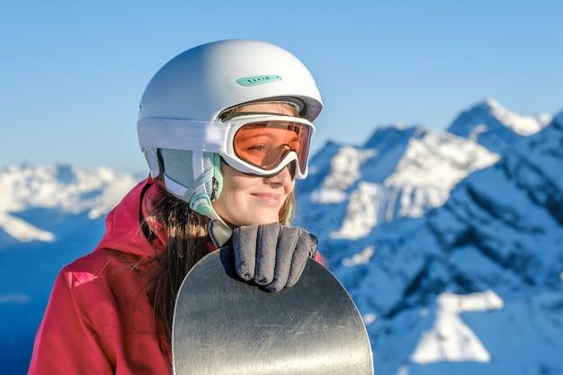 Snowboarder della donna che sta con lo snowboard. ritratto del primo piano