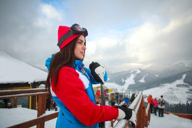 Snowboarder della donna in inverno alla stazione sciistica e al cielo