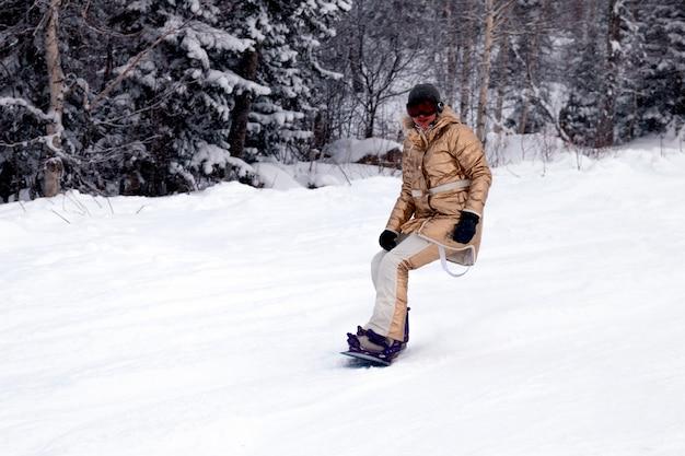 Snowboarder della donna professionale in abiti sportivi luminosi ed attrezzatura che scia in discesa in alte montagne soleggiate nevose. sfocatura, soft focus, oggetto in movimento
