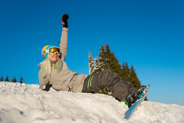 Snowboarder della ragazza che si siede in cima al pendio, sorridendo e rilassandosi all'aperto sulla neve