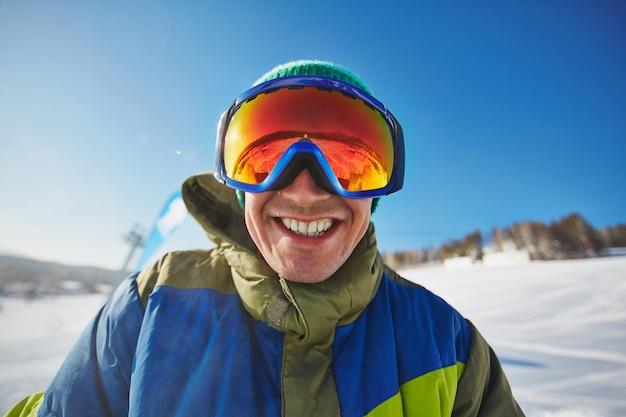 Snowboarder felice godendo di una giornata sulla neve