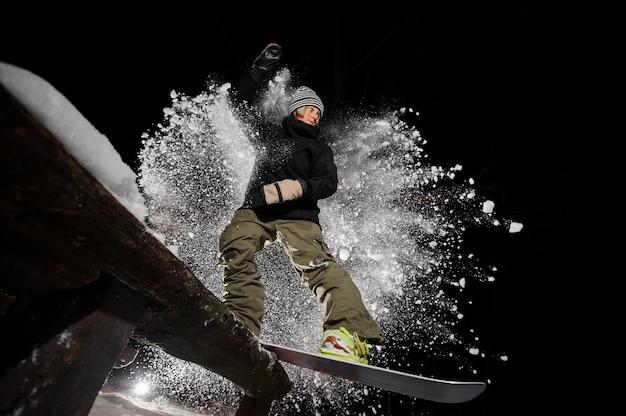 Snowboarder femminile attivo a cavallo lungo il pendio della montagna di notte