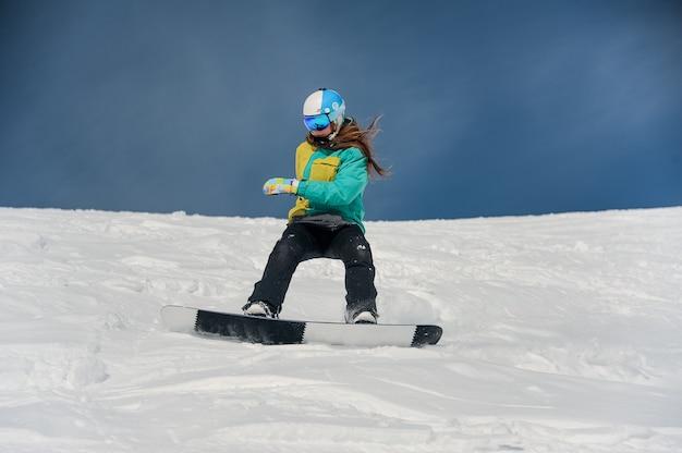 Snowboarder femminile che guida giù il pendio di montagna