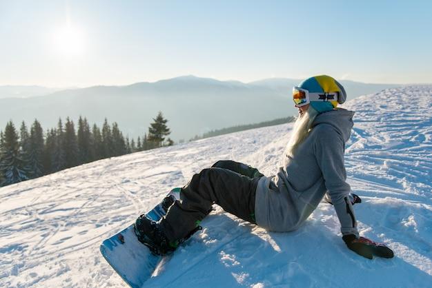 Snowboarder femminile che si siede sul pendio nevoso la sera, godendo della giornata di sole in montagna