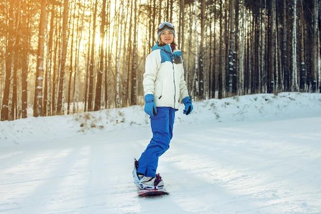 Snowboarder femminile che snowboard giù la montagna