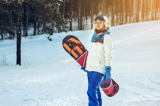 Snowboarder femminile insieme a snowboard tra gli alberi