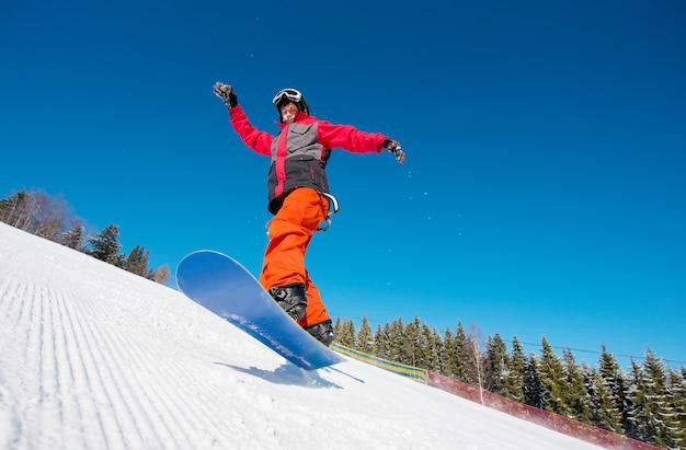 Snowboarder in aria durante la guida sul pendio in montagna in una bella giornata di sole invernale