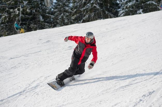 Snowboarder maschio cavalcando giù dalla montagna in giornata invernale