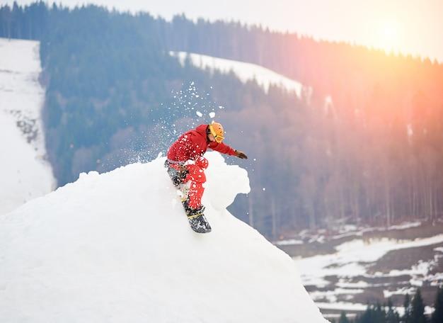Snowboarder maschio che guida dalla cima della collina nevosa con lo snowboard alla stazione sciistica invernale