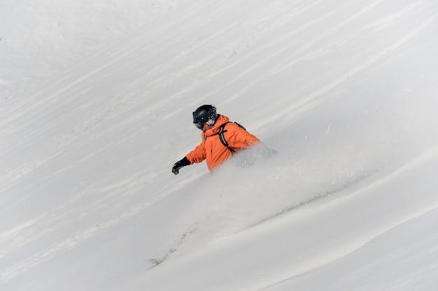 Snowboarder maschio che guida giù il pendio della neve