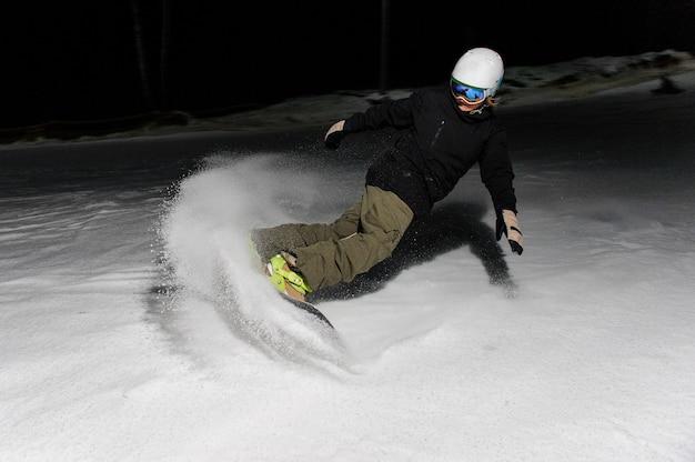 Snowboarder maschio che guida giù il pendio di montagna di notte