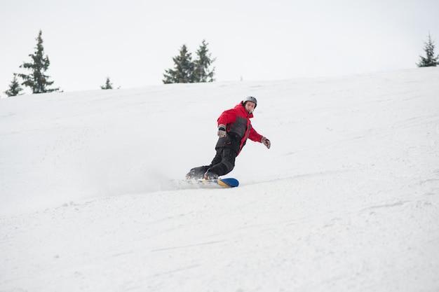 Snowboarder maschio che guida sopra il pendio sul pendio nevoso