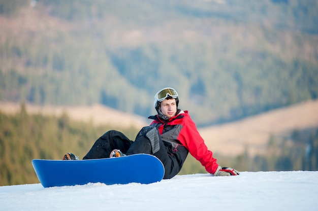 Snowboarder maschio con lo snowboard che si siede sul pendio nevoso