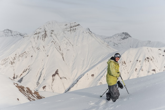 Snowboarder maschio sorridente sulle cime delle montagne