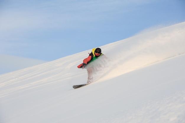 Snowboarder professionista che guida giù per il pendio nevoso