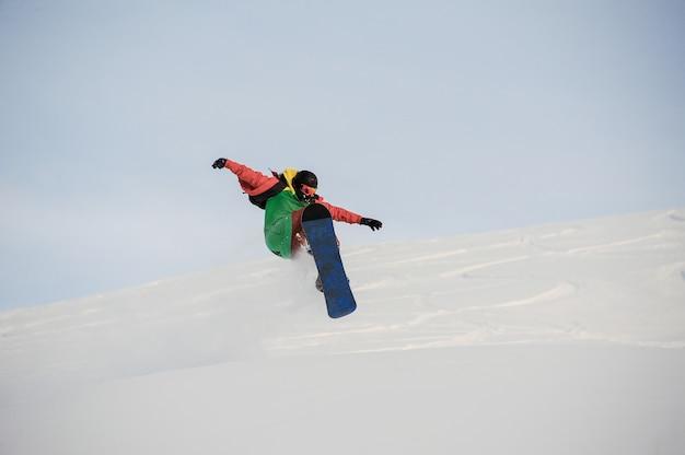 Snowboarder professionista che salta sulla neve farinosa