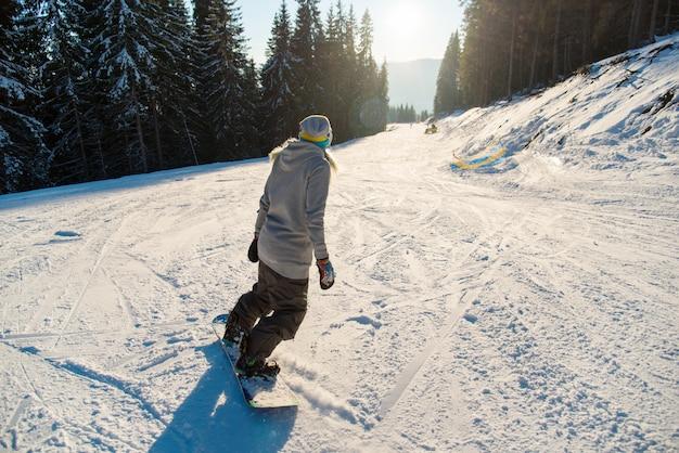 Snowboarder sciare la pista in giornata di sole invernale