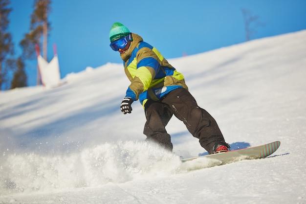 Snowboarder scorrevole dalla montagna in giornata invernale