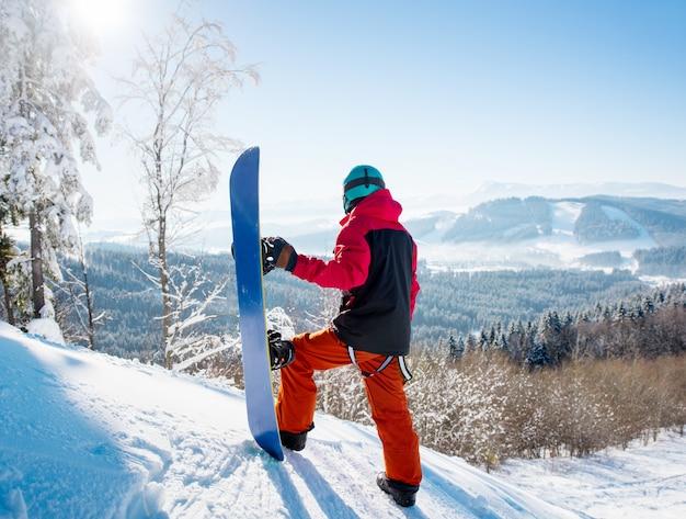 Snowboarder sulla cima di un pendio guardando intorno godendo la vista sulla stazione sciistica invernale