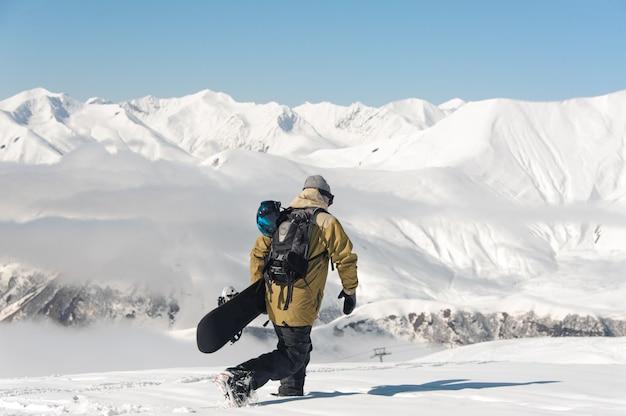 Snowboarder sulle montagne e sul cielo blu di inverno.