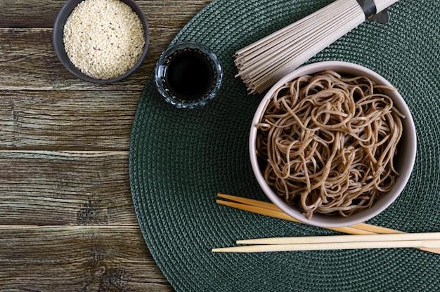 Soba freddo (pasta di grano saraceno) con salsa e sesamo. cibo giapponese. cucina asiatica tradizionale - tagliatelle di farina di grano saraceno. vista dall'alto, piatto.