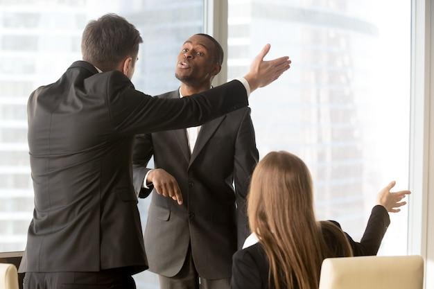 Soci commerciali infastiditi che discutono durante la riunione