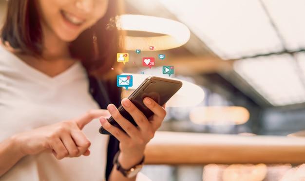 Social media e donna asiatica online e sorridente digitale che per mezzo dell'icona di tecnologia dello spettacolo e dello smartphone.