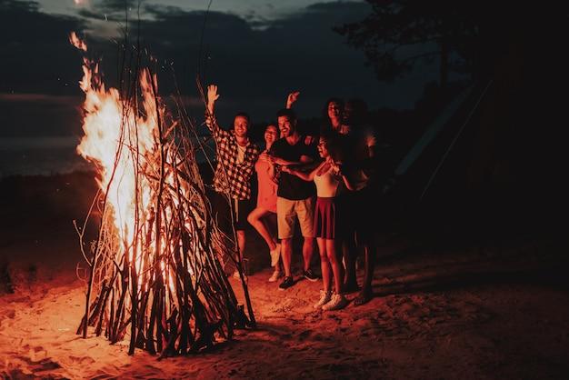 Società di svago di festa che si scalda intorno al falò sulla spiaggia.