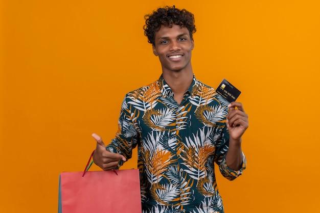 Soddisfatto giovane bello di carnagione scura con capelli ricci in foglie camicia stampata sorridenteholding borse per la spesa che mostra la carta di credito mentre in piedi su uno sfondo arancione