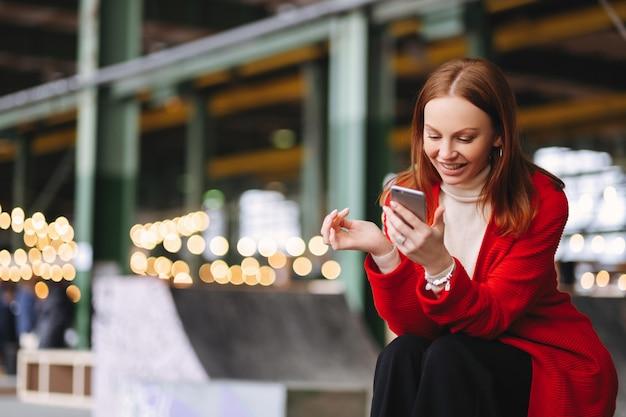 Soddisfatto giovane donna europea in cappotto rosso, detiene il telefono cellulare