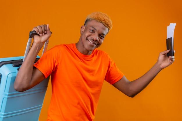 Soddisfatto giovane ragazzo bello che indossa la maglietta arancione che tiene la valigia di viaggio e biglietti aerei sorridendo felice e positivo in piedi sopra la parete arancione