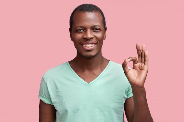 Soddisfatto maschio dalla pelle scura con felice espressione, gesti con la mano come mostra segno ok, dimostra che tutto va bene, mostra approvazione, isolato su rosa
