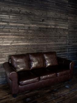 Sofà di cuoio marrone d'annata su una parete e su un pavimento di legno
