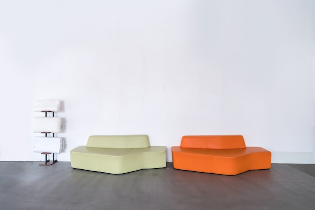 Sofà moderno arancio e verde nella stanza vuota