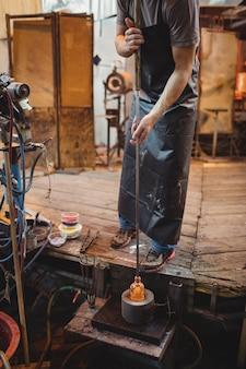 Soffiatore di vetro usando la muffa per modellare un vetro fuso