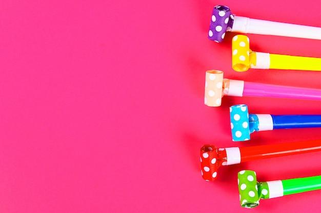 Soffiatori di partito multicolor su fondo rosa. fischi da festa multicolori. decor per una festa di compleanno