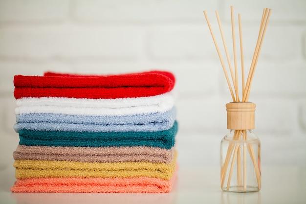 Soffici asciugamani sul tavolo di legno chiaro con bastoncini di aroma