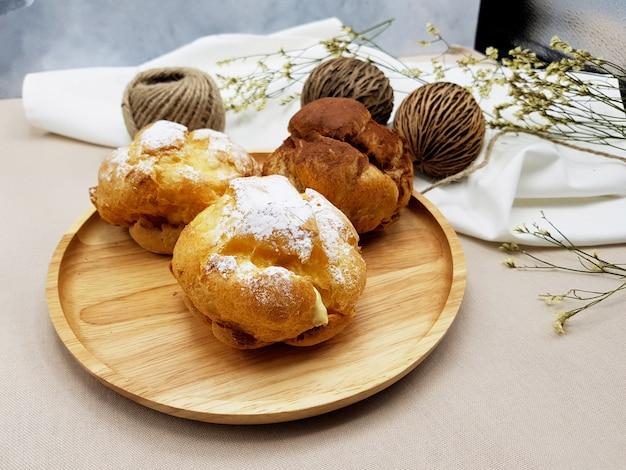Soffio crema dei choux del cioccolato e della vaniglia sul piatto di legno