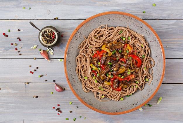 Soffriggere da cuori di pollo, paprika, cipolle e noodles di grano saraceno. vista dall'alto