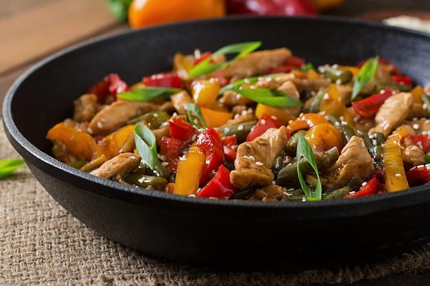 Soffriggere pollo, peperoni e fagiolini