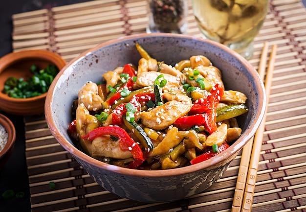 Soffriggere pollo, zucchine, peperoni e cipolla verde